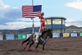 One of the Riata Ranch Cowboy Girls riding in the flag at the presentation of the colors at the beginning of the rodeo at the County Fair.